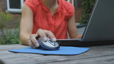 Young woman uses laptop outside.