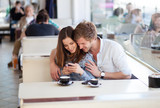 Young couple in love surfing the web / looking at photos on mobi
