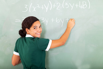 smiling student writing mathematics on the blackboard