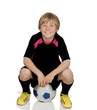 Preteen with a uniform for play soccer sitting on a ball