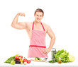 Sexy muscular man wearing a red apron and preparing a salad