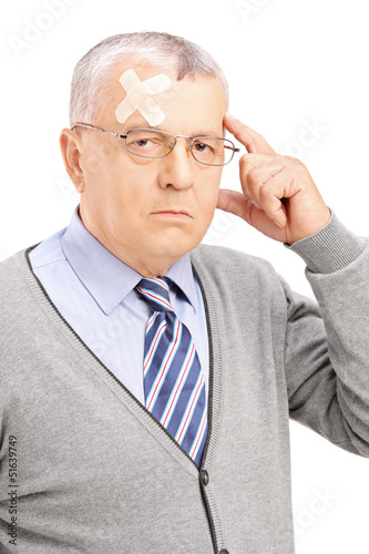 Portrait of a mature gentleman with headache looking at camera
