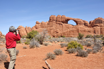 Man Taking a Photo of the Skyline Arch in Arches National Park