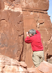 Man Taking Photograph of Petroglyph Panel