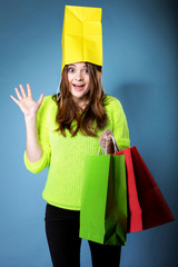 Surprised girl paper shopping bag on head. Sales.