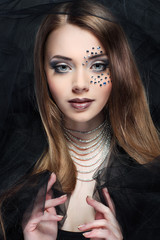 Portrait of beautiful girl with strasses on face,on a dark-grey