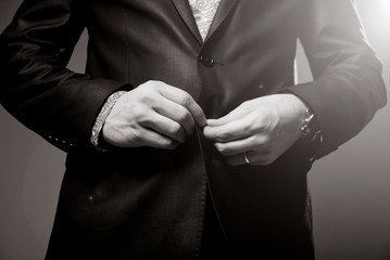 Business man tidy up his suit's button, makes a neat image