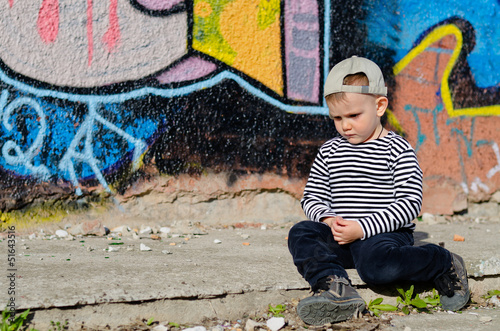 Small boy sitting thinking or sulking