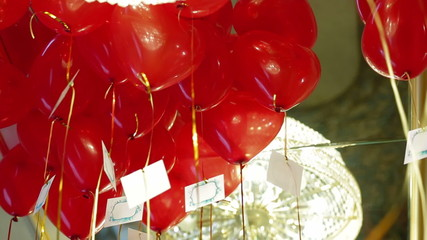 Lots of heart shaped balloons flying in a room