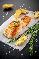 Grilled salmon and baked potatoes on a slate blackboard