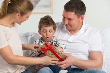 Couple giving gift to their little son in the living room. Happy