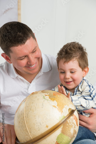 Father and son looking at globe at home and having fun