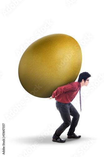 Businessman carry gold egg on white