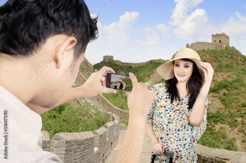 Asian tourist posing in front of the Great Wall China