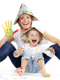 Cute boy and mother have coloured hands, playing together