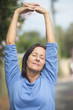 Happy relaxed mature woman arms up
