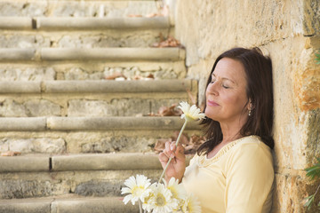 Romantic mature woman in love with flower