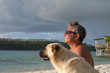 Dog and man on tropical paradise white sand beach sunset