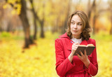 young woman writing verses in autumn park  poster