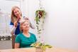 junge Frau kämmt Seniorin das Haar