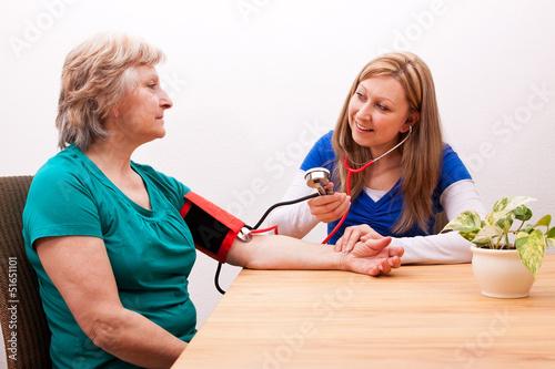Pflegerin misst Seniorin den blutdruck