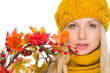 Portrait of girl in hat and scarf holding autumn bouquet
