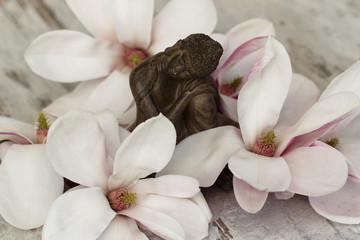 Buddhafigur mit Magnolienblüten