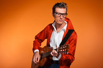 Retro fifties musician with glasses playing acoustic guitar.
