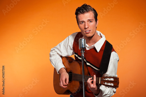 Retro fifties rock and roll singer playing acoustic guitar.