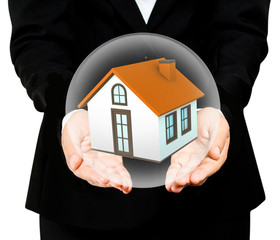 hands saving small house in glass ball