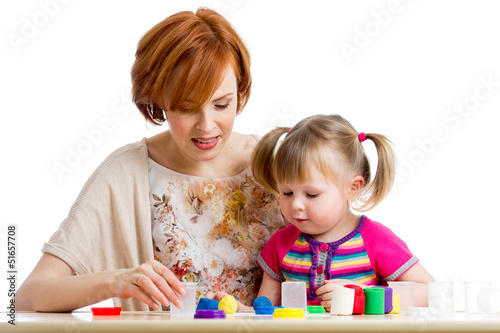Happy kid girl and mother playing with colorful clay toy