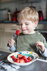 Little boy eating fresh strawberries