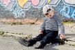 Lonely little boy sitting on the sidewalk