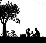 Romantic couple in picnic with bikes in park in spring
