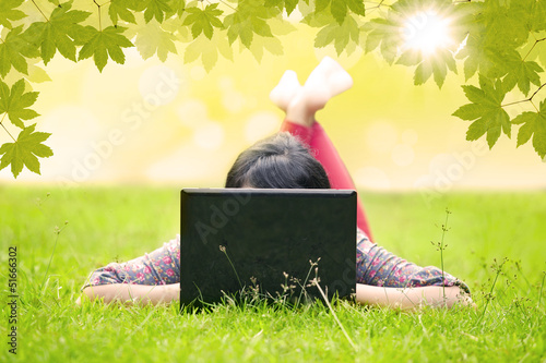 Asian student looking at laptop on green grass