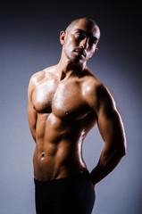 Muscular man in dark studio