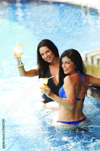 Two women with cocktails in swimming pool
