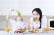 Mother and boy eating salad at home