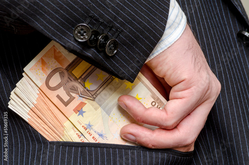 Business man putting bribe money in his jacket pocket.