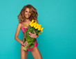 Beautiful woman in pink swimsuit with bouquet of yellow tulips