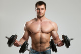 Handsome guy working out with dumbbells