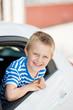 kleiner junge schaut aus dem auto