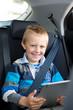 kleiner junge mit tablet im auto