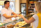 Shopkeeper giving pastry to customer