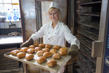 Fototapety Baker in bakehouse or bakery putting bread in the oven