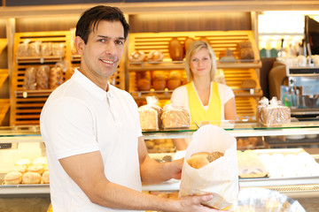 Happy customer in bakery with bags of bread