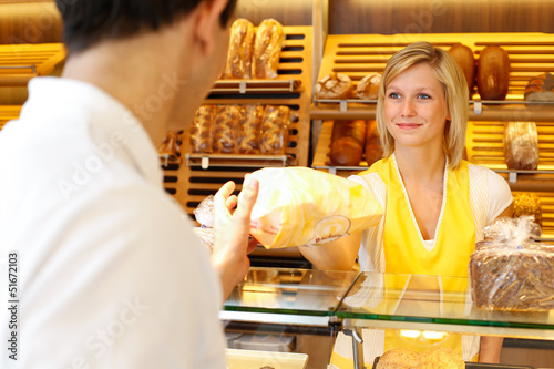 Baker's shop shopkeeper gives bread to customer