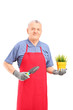 Mature man with apron holding a plant and a spade