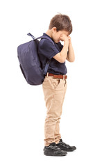 Full length portrait of a schoolboy crying