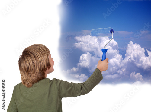 Adorable child painting a beautiful sky with a roller